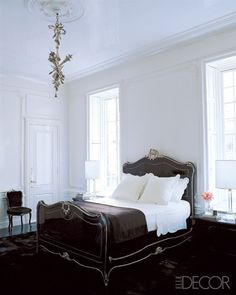 White walls and bedding paired with a black headboard