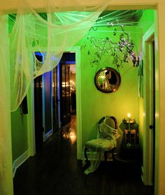 Halloween lighting to haunt your house .Concept for eerie lighting in green, purple, red, blue lightbulbs placed in alcove light fixtures then diffused through cheesecloth or muslin. Be careful with spider-webbing, may catch fire. Halloween 2018, Soirée Halloween, Halloween Birthday, Halloween Party Decor, Holidays Halloween, Halloween Lighting, Halloween Entryway, Halloween Ceiling Decorations, Hallway Decorations