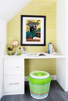 Built-in white desk in kids room with storage, bright stool seating, and elephant decor.