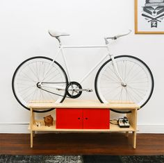 If the amount of space your bike takes up in your tiny apartment is making you nuts, you'll love this collection of bike rack furniture.: Bike Storage Furniture: A Double Duty Console Bike Storage Bookshelf, Bike Storage Living Room, Bike Storage Furniture, Bike Storage Apartment, Space Saving Furniture, New Furniture, Furniture Plans, Furniture Design, Furniture Dolly