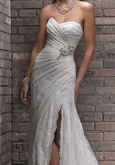 This beautiful ivory 2013 Maggie Sottero Myra dress has a high scalloped side slit, showing off one leg and it has a corset back. I had a professional sew the jeweled belt on so it stays in place. The