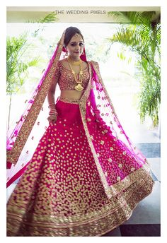 Twirling Bride - Pink Bright Bridal Lehenga | WedMeGood | Sequinned Bridal Lehenga with a Pink Blouse and Pink Net Dupatta, Gold Jewelry #wedmegood #indianwedding #indianbride #pink #lehenga #gold