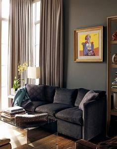 love it all: dark couch, dark wooden floor, glass table, dark wall, light beige curtains, small table in the corner with orchid and rectangle lamp, colorful painting! and no carpet...
