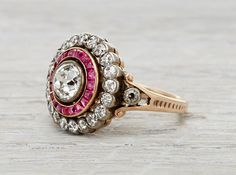 Late Victorian ring made in silver on gold centered with an approximately .80 caratEGL certified old European cut diamond with H-I color and VS2 clarity. Accented by rubies and old Europeandiamonds.Circa 1900.