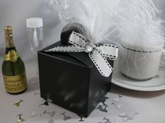 Black silk balloon weight favour box with white with black stitching ribbon, white feather & clear heart gem