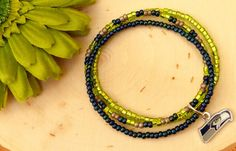 You will receive a lot of compliments on this beautiful stacked bracelet as you cheer on the Seattle Seahawks! This is a beautiful handmade piece carefully crafted by Blossom with Hope. Designed with shades of bright green, blue and silver seed beads. This beautiful 3-piece set is the perfect gift for any Seahawks' fan!  Product Details: Style ~ Beaded, Stretch Colors ~ Shades of bright green, blue and silver  Accents ~ Official NFL charm