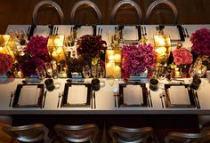<p>Pillar candles are placed in mirrored containers to enhance their glow. The candles and pink and purple flowers are all set on a mirrored runner that runs the length of the table.</p><p><i>(Photo: Colin Miller)</i></p>