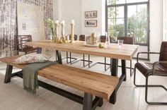 une table en bois massif clair et un banc en bois dans la salle à manger