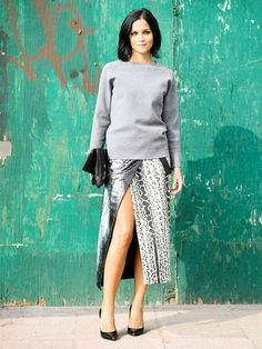 Leigh Lezark wears a gray sweater, snake-print wrap skirt, foldover clutch, and pointed-toe pumps