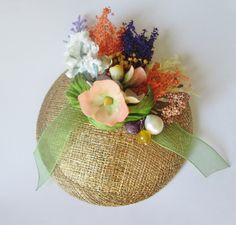 Tocado pequeño con perla, piedra natural, cinta de organza, flores de porcelana y secas. Base de rafia dorada.