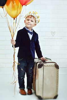 Handsome little boy in a king's crown with balloons and a suitcase