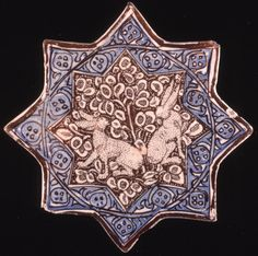 Eight-pointed star tile. Fritware (stonepaste), painted in blue and lustre over an opaque white glaze. The central field is decorated in reserve against a  lustred background with two hares and foliage. The border is decorated with a frieze of dotted medallions and scrolls, outlined in lustre, coloured in blue and enclosed within lustre lines. Reverse undecorated.