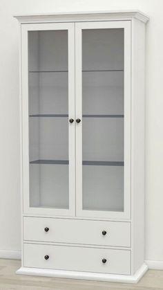 Paris Vitrineskab - Vitrineskab i hvid melamin i romantisk stil. Vitrineskabet har 2 elegante glaslåger og 2 brede skuffer med flotte metalgreb i antik-look. Bag glaslågerne befinder der sig 3 glashylder der kan justeres efter behov.