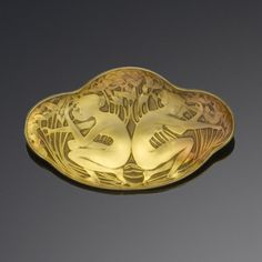 A glass brooch, by Lalique, first quarter of the 20th century  The cast and foiled golden-orange glass plaque depicting two crouching maidens amongst flowers and foliage, signed Lalique, maker's mark, diameter 5.5cm.