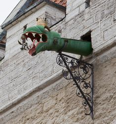 Dragon-headed gargoyle of the Tallinn Town Hall, Estonia.  In architecture, a gargoyle is a carved or formed grotesque with a spout designed to convey water from a roof and away from the side of a building, thereby preventing rainwater from running down masonry walls and eroding the mortar between.