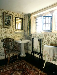 Traditional bathroom in a English country home with a pretty floral wallpaper