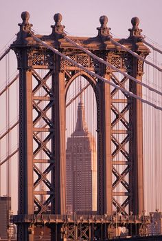 An iconic view of the Manhattan Bridge and Empire State Building in NYC.