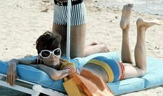 The always fair and beautiful Audrey Hepburn looking so colorful at the beach....Check out those huge sunglasses...and the cute short hair cut...