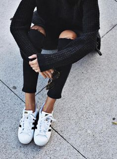 Skinny ripped jeans, a black sweater, and stylish adidas