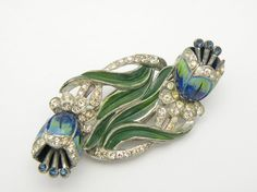 Marvelous silver tone plated Coro Duette designed by Gene Verrecchio and patented in 1942 with the number of 131976. This lovely piece features beautiful blue enameled tulips decorated with crystal rhinestones around the top and bottom of the flower. The stamens are topped with dark sapphire rhinestones. Green enamel decorates the flowing leaves of the tulip.