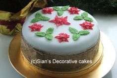 Christmas cake with red poinsettias and green holly leaves - how easy but effective is that?!  http://stores.ebay.co.uk/Purple-Butterfly-Cake-Toppers