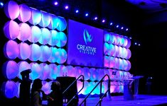 """Cylindrical shapes with colorful LED lighting variations add texture to any event backdrop. Love this concept? Check out our """"Creative Visions Transformation"""" board for more event decor ideas!"""