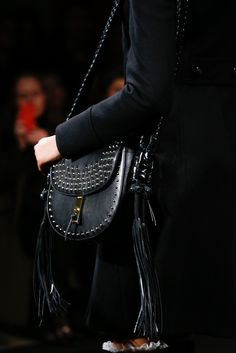 Fall '15 Accessories Trend Report | Fringe Elements | Altuzarra Black Studded Leather Saddle Bag with a Brass Closure and Fringe Hanging From Each Side of the Shoulder Strap