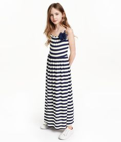 Jersey maxi dress with narrow shoulder straps, elasticized seam at waist, and gently flared skirt. Unlined.