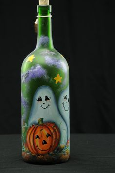 This handpainted Halloween bottle features two cute ghosts, bats and a very happy pumpkin out for a night on the prowl or perhaps a night of trick or treating. While a fun and beautiful piece when unlit, when the bottle is plugged in it transforms into a beautiful lamp giving it a very different look.  The lights are fed in through a small hole in the back of the bottle so no wires are visible from the front.  The lights should last for a long time. If ever in need of a new strand, a…