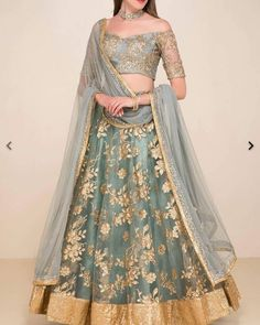 The bardot neckline blouse is adorned with floral sequin embroidery. It is paired with a net flared embroidered lehenga and net dupatta. gold grey blue silver by collective lengha Lehenga Choli, Lehenga Indien, Lehnga Dress, Indian Lehenga, Indian Gowns, Indian Attire, Green Lehenga, Sari, Black Lehenga