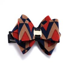 Treat your tresses to this decorative hair bow. Featuring an intricate bow with a bold geometric design, this accessory serves both fashion and function needs.
