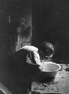 Thurston Hopkins: Liverpool Slums, November 1956  A woman washing her face over a basin in her rundown Liverpool home