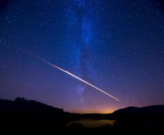 Meteor streaking across the sky above a Scottish loch at Galloway Forest Park, South Ayrshire