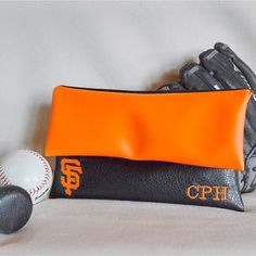 Are you a San Francisco Giants fan?!?! Then this is the perfect personalized clutch for you. This handbag is just the right size for game days at the park or showoff your team in style with the added touch of monogramming. Made with a black vegan leather pouch and orange vegan leather flap, this is a must have! As well as the addition of personalization with the San Francisco Giants team logo and names/initials, each clutch is lined with a baseball cotton material making each clutch uniq...