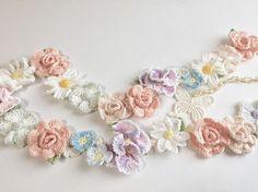 コーラルピンクの薔薇の花・クレマチス・アスター・パンジーや小花などをたっぷりと飾ったネックレスです。 長さは約90cm。チェーン部分を長く約20cmとってありますので、2連のお使いも楽しんでいただけます。チェーンはお肌に優しいエアリーチェーン使用です。(樹脂のチェーンを繊維でコーティングされたものでとても軽いです)テール部分には繊細な蝶々のモチーフ付。 チェーンを前に垂らしていただくと留める位置によって蝶がお花の横で揺れたり、お花に留まったりの表情がお楽しみいただけます