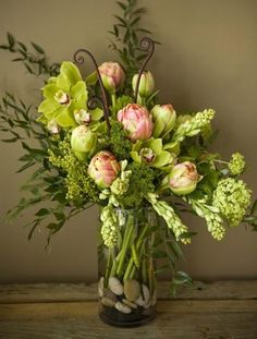Orchids, fern green tropicals, vibernum combined to make a breathtaking still life.
