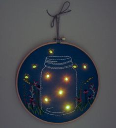 """Nightlight Embroidered Wall Art by The Monster's Lounge on Scoutmob Shoppe. $60 A mason jar and colorful meadow of flowers are embroidered onto the blue felt, which also features real blinking firefly lights. Each one is handmade, so slight variations may occur. - Hoop measures 8"""" in diameter. - Made from wood, with a metal tightener. - Switch at the back turns on flashing fireflies. - Do not remove from hoop."""