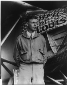 Charles A. Lindbergh  (1902-1974) American aviator famous for piloting the first non-stop solo flight from New York to Paris 20-21 May 1927; an event that brought him unprecedented international celebrity, due to the emerging role of mass media in the lives of the public.  Nicknamed, 'Lucky Lindy' he is shown here with the Spirit of St. Louis (his famous plane) in background