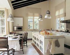 Cocina blanca con isla central, con encimeras de mármol, lámparas metálicas y comedor