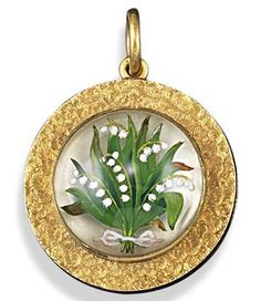 A late Victorian reverse carved crystal mounted gold circular locket pendant, depicting lily of the valley