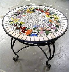 Coffee tables looks great when adorned with mosaic art designs. This coffee table is beautifully adorned with floral mosaic design. A combination of dark and soft colors is used for the flowers. Leaves are given natural light and dark green. The white tiles in the base are giving prominence to the floral design.