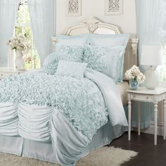 Ruffled comforter set with hand-sewn detailing in blue.  Product: One comforter, one bed skirt and two pillow shamsC...