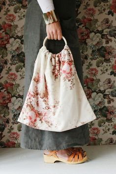 Meet Millie...she is a rather pretty knitting bag made from a rare vintage floral print.  Not only does she like knitting but she likes to be taken out for tea and she likes to think she is not only a bag but a rather pretty accessory to your daily wear.  When not in use she likes to be hung on a wall so all can share in her beauty.She is approx 45cm wide at her widest point.She will arrive wrapped in tissue in her own personal box.  This box is then wrapped in Kraft Paper t...