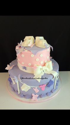 Baby shower cake. Fondant baby booties. Butterflies, baby clothes, and bow. www.facebook.com/cakesbyelise