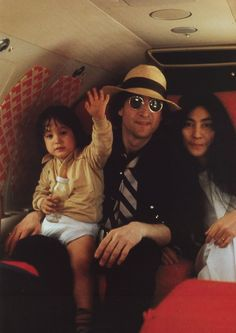 John Lennon on a plane with Yoko Ono and young Sean, 1970s.