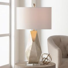 Striking with modern flair, this geometric table lamp sits on a clear acrylic base.