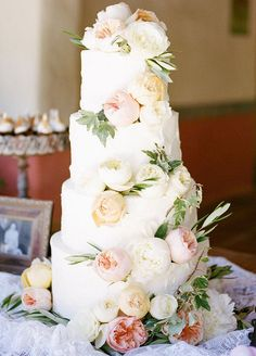 10 Wedding Cakes We Love For Summer: Take a slice of romance, soft pink and cream blooms cascade down this charming 4-tiered cake.