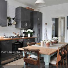 Kontrastreiche Einblicke gewährt diese Küche, in der die modernen grauen Schränke auf einen traditionellen Esstisch aus Holz treffen. Die mintfarben gestrichenen…
