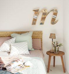 Dormitorio con cabecero de fibra vegetal y lámpara de pared con forma de…