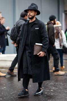 An on-trend young man on the streets of London wearing an all black menswear outfit.